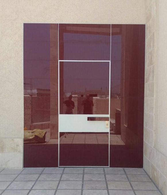 דלת כניסה מסדרת קו אפס הכוללת חיפוי קיר בזכוכית תואמת את הדלת.