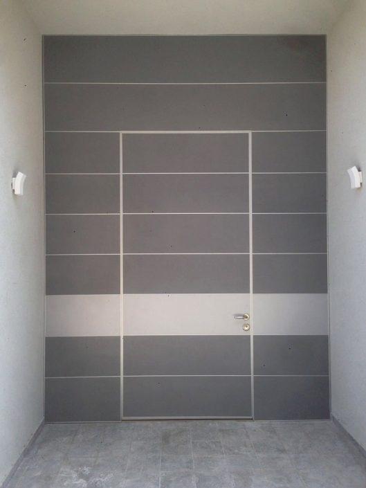 דלת פלדיניום בקו אפס המשתלבת עם חיפוי קיר הכניסה.