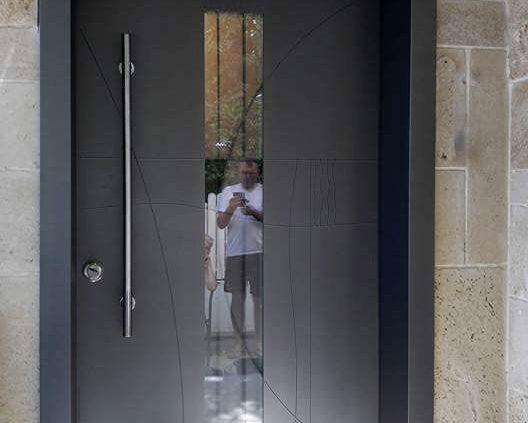 דלת כניסה מעוצבת בטכניקה יחודית המשלבת חלון סורג לייזר