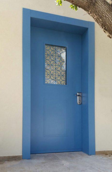 דלת כניסה כחולה עם חלון סורג מעוצב צבוע בגוון הדלת